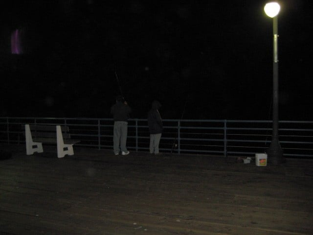 Two people fishing from Pier. These guys are dangerous for surfers.